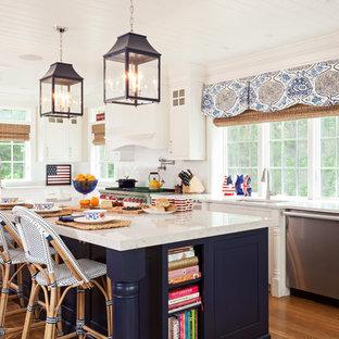Immagine di una cucina lineare stile marino con ante bianche, paraspruzzi bianco, elettrodomestici in acciaio inossidabile, isola, lavello sottopiano, ante in stile shaker e pavimento in legno massello medio
