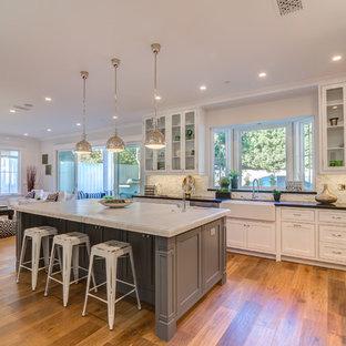 Große Klassische Wohnküche in U-Form mit Landhausspüle, Glasfronten, weißen Schränken, Mineralwerkstoff-Arbeitsplatte, bunter Rückwand, Rückwand aus Porzellanfliesen, Küchengeräten aus Edelstahl, braunem Holzboden und Kücheninsel in Los Angeles