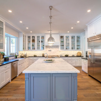 Example of a large transitional u-shaped medium tone wood floor eat-in kitchen design in Los Angeles with a farmhouse sink, glass-front cabinets, white cabinets, solid surface countertops, multicolored backsplash, porcelain backsplash, stainless steel appliances and an island