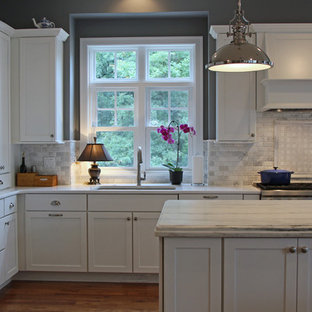 This is an example of a large traditional l-shaped eat-in kitchen in Milwaukee with a single-bowl sink, recessed-panel cabinets, white cabinets, marble benchtops, white splashback, stone tile splashback, panelled appliances, medium hardwood floors and multiple islands.