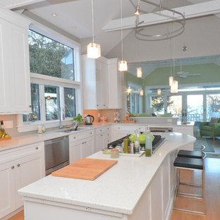 Diseño de cocina clásica renovada, grande, abierta, con fregadero bajoencimera, armarios con paneles empotrados, puertas de armario blancas, encimera de terrazo, electrodomésticos de acero inoxidable, suelo de madera clara, una isla y encimeras blancas
