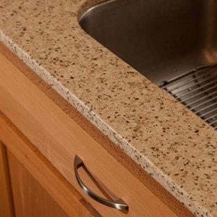 Klassisk inredning av ett litet kök, med en undermonterad diskho, skåp i shakerstil, skåp i ljust trä, bänkskiva i återvunnet glas, beige stänkskydd, stänkskydd i keramik, vita vitvaror, ljust trägolv och en köksö