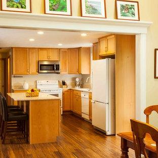 Modelo de cocina comedor en L, tradicional, pequeña, con fregadero bajoencimera, armarios estilo shaker, puertas de armario de madera clara, encimera de vidrio reciclado, salpicadero beige, salpicadero de azulejos de cerámica, electrodomésticos blancos, suelo de bambú y una isla