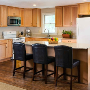 Small traditional eat-in kitchen photos - Small elegant l-shaped bamboo floor eat-in kitchen photo in Boston with an undermount sink, shaker cabinets, light wood cabinets, recycled glass countertops, beige backsplash, ceramic backsplash, white appliances and an island