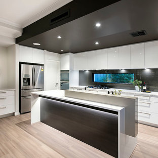 Photo of a large contemporary galley open plan kitchen in Perth with flat-panel cabinets, white cabinets, quartz benchtops, black splashback, window splashback, stainless steel appliances, light hardwood floors, multiple islands, brown floor and white benchtop.
