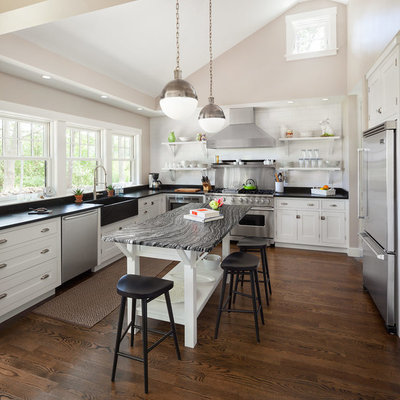 Example of a transitional u-shaped kitchen design in Portland Maine with a farmhouse sink, recessed-panel cabinets, white cabinets, white backsplash, subway tile backsplash and stainless steel appliances