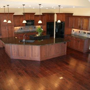Bild på ett stort vintage kök, med en dubbel diskho, luckor med infälld panel, skåp i mörkt trä, granitbänkskiva, beige stänkskydd, stänkskydd i keramik, svarta vitvaror, mörkt trägolv, flera köksöar och blått golv