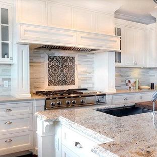 Bild på ett stort vintage kök, med rostfria vitvaror, vita skåp, bänkskiva i kvarts, en undermonterad diskho, luckor med profilerade fronter, grått stänkskydd, mellanmörkt trägolv, en köksö och stänkskydd i marmor