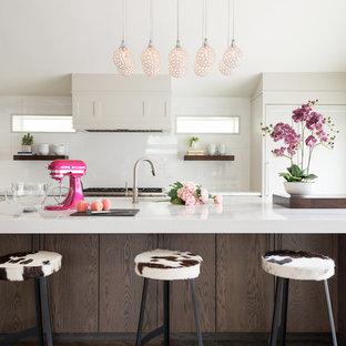 Transitional kitchen designs - Transitional kitchen photo in Salt Lake City with shaker cabinets, beige cabinets, white backsplash, glass sheet backsplash and an island