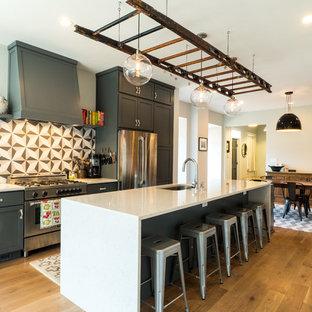 ワシントンD.C.の大きいトランジショナルスタイルのおしゃれなキッチン (アンダーカウンターシンク、シェーカースタイル扉のキャビネット、グレーのキャビネット、マルチカラーのキッチンパネル、シルバーの調理設備の、無垢フローリング、クオーツストーンカウンター、セメントタイルのキッチンパネル、茶色い床) の写真