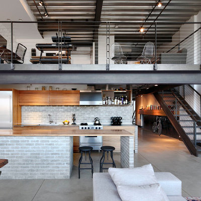 Small urban galley concrete floor and gray floor open concept kitchen photo in Seattle with an island, flat-panel cabinets, light wood cabinets, wood countertops, gray backsplash, brick backsplash, stainless steel appliances and an undermount sink