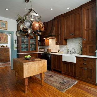 Свежая идея для дизайна: угловая кухня среднего размера в классическом стиле с раковиной в стиле кантри, фасадами с утопленной филенкой, темными деревянными фасадами, белым фартуком, фартуком из каменной плитки, паркетным полом среднего тона, островом и коричневым полом - отличное фото интерьера