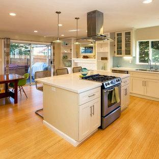 Idee per una cucina stile marinaro di medie dimensioni con lavello sottopiano, ante in stile shaker, ante beige, top alla veneziana, paraspruzzi blu, paraspruzzi con piastrelle in ceramica, elettrodomestici in acciaio inossidabile, parquet chiaro e isola