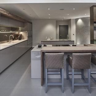 Inredning av ett modernt stort linjärt kök och matrum, med en nedsänkt diskho, släta luckor, beige skåp, bänkskiva i kvartsit, brunt stänkskydd, spegel som stänkskydd, rostfria vitvaror, klinkergolv i porslin, flera köksöar och grått golv