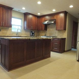 Foto di una cucina classica di medie dimensioni con lavello sottopiano, ante in stile shaker, ante marroni, top in granito, paraspruzzi beige, paraspruzzi con piastrelle in ceramica, elettrodomestici in acciaio inossidabile, pavimento con piastrelle in ceramica e isola