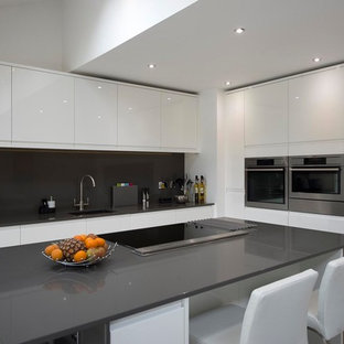 This is an example of a medium sized modern l-shaped kitchen/diner in Other with a submerged sink, flat-panel cabinets, white cabinets, quartz worktops, grey splashback, stone slab splashback, stainless steel appliances, ceramic flooring, an island and beige floors.