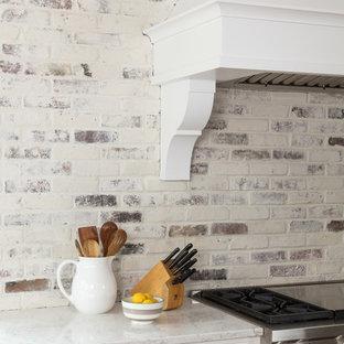 ボストンの広いコンテンポラリースタイルのおしゃれなキッチン (エプロンフロントシンク、シェーカースタイル扉のキャビネット、白いキャビネット、大理石カウンター、白いキッチンパネル、レンガのキッチンパネル、シルバーの調理設備、無垢フローリング、茶色い床) の写真
