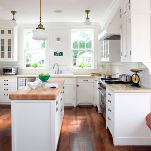 Inspiration for a mid-sized country u-shaped kitchen in Boston with a drop-in sink, shaker cabinets, white cabinets, white splashback, subway tile splashback, stainless steel appliances, with island, tile benchtops, dark hardwood floors and brown floor.