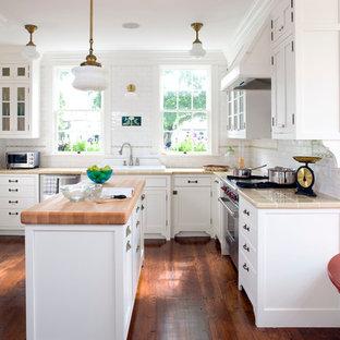 Idéer för att renovera ett mellanstort lantligt u-kök, med en nedsänkt diskho, skåp i shakerstil, vita skåp, vitt stänkskydd, stänkskydd i tunnelbanekakel, rostfria vitvaror, en köksö, kaklad bänkskiva, mörkt trägolv och brunt golv