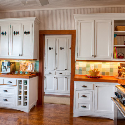 Mid-sized island style galley dark wood floor and brown floor eat-in kitchen photo in Miami with wood countertops, green backsplash, a farmhouse sink, shaker cabinets, white cabinets, glass tile backsplash and no island