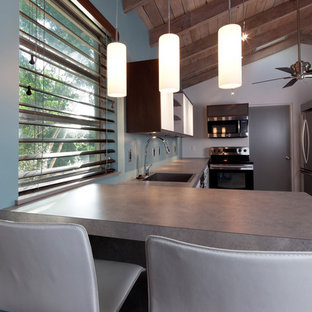 Photo of a mid-sized contemporary single-wall open plan kitchen in Other with an undermount sink, flat-panel cabinets, white cabinets, concrete benchtops, blue splashback, white appliances, light hardwood floors and a peninsula.