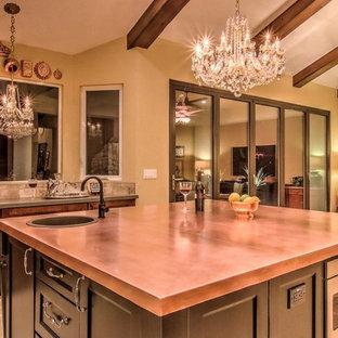 Foto de cocina comedor bohemia, de tamaño medio, con fregadero de un seno, puertas de armario negras, encimera de cobre, electrodomésticos de acero inoxidable, suelo de baldosas de porcelana, una isla y suelo beige