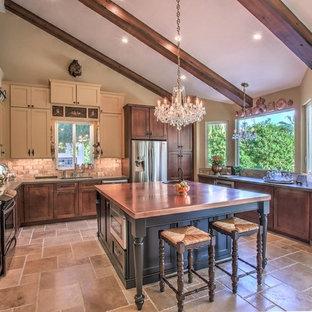フェニックスの中くらいのエクレクティックスタイルのおしゃれなキッチン (シングルシンク、シェーカースタイル扉のキャビネット、黒いキャビネット、銅製カウンター、ベージュキッチンパネル、トラバーチンのキッチンパネル、シルバーの調理設備、磁器タイルの床、ベージュの床) の写真