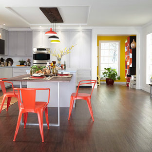 Large contemporary eat-in kitchen appliance - Example of a large trendy u-shaped medium tone wood floor eat-in kitchen design in Raleigh with two islands, flat-panel cabinets and white cabinets