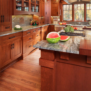 Large craftsman eat-in kitchen inspiration - Example of a large arts and crafts l-shaped medium tone wood floor and brown floor eat-in kitchen design in New York with a farmhouse sink, shaker cabinets, medium tone wood cabinets, wood countertops, green backsplash, subway tile backsplash, stainless steel appliances, an island and brown countertops