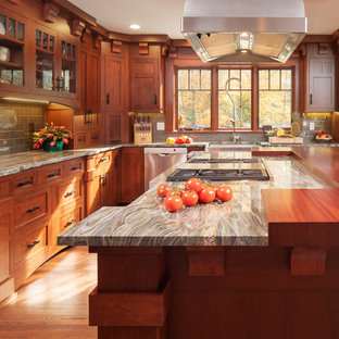 Design ideas for a large arts and crafts l-shaped eat-in kitchen in New York with a farmhouse sink, shaker cabinets, medium wood cabinets, wood benchtops, green splashback, subway tile splashback, stainless steel appliances, medium hardwood floors, with island, brown floor and brown benchtop.