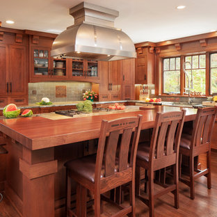 Large craftsman kitchen ideas - Kitchen - large craftsman l-shaped medium tone wood floor and brown floor kitchen idea in New York with a farmhouse sink, shaker cabinets, medium tone wood cabinets, wood countertops, green backsplash, subway tile backsplash, stainless steel appliances, an island and brown countertops