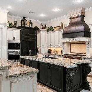 オーランドの大きい地中海スタイルのおしゃれなキッチン (アンダーカウンターシンク、レイズドパネル扉のキャビネット、ベージュキッチンパネル、白いキャビネット、御影石カウンター、黒い調理設備、トラバーチンの床) の写真