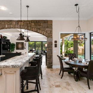 Idéer för stora medelhavsstil kök, med en undermonterad diskho, luckor med upphöjd panel, vita skåp, granitbänkskiva, beige stänkskydd, svarta vitvaror, travertin golv och flera köksöar