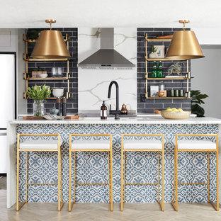 ソルトレイクシティのコンテンポラリースタイルのおしゃれなキッチン (黒いキッチンパネル、レンガのキッチンパネル、シルバーの調理設備、淡色無垢フローリング、ベージュの床、白いキッチンカウンター) の写真