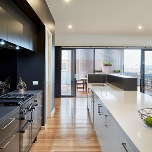 Contemporary galley kitchen in Melbourne with an undermount sink, flat-panel cabinets, black cabinets, black splashback, black appliances, light hardwood floors, with island and beige floor.