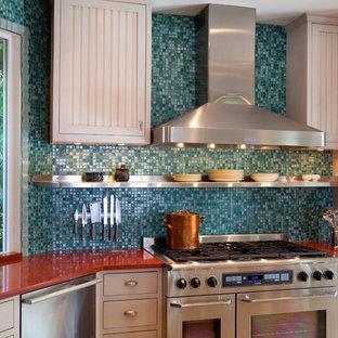 Ispirazione per una cucina abitabile tropicale di medie dimensioni con lavello sottopiano, ante con riquadro incassato, ante bianche, top in vetro riciclato, paraspruzzi blu, elettrodomestici in acciaio inossidabile e isola
