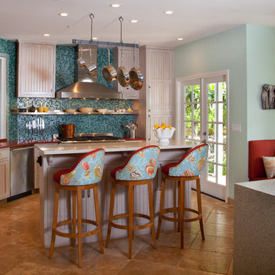 Example of a mid-sized island style l-shaped eat-in kitchen design in San Diego with an undermount sink, recessed-panel cabinets, white cabinets, blue backsplash, mosaic tile backsplash, stainless steel appliances, an island and recycled glass countertops