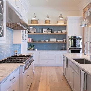 Diseño de cocina comedor en L, clásica renovada, grande, con fregadero bajoencimera, armarios estilo shaker, puertas de armario blancas, encimera de cuarzo compacto, salpicadero azul, salpicadero de azulejos tipo metro, electrodomésticos con paneles, suelo de madera en tonos medios y una isla