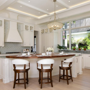 Photo of a transitional l-shaped open plan kitchen in Miami with a farmhouse sink, shaker cabinets, white cabinets, grey splashback, subway tile splashback, panelled appliances, medium hardwood floors, with island, brown floor, grey benchtop and coffered.