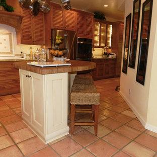 マイアミの大きいトロピカルスタイルのおしゃれなキッチン (エプロンフロントシンク、ルーバー扉のキャビネット、中間色木目調キャビネット、白いキッチンパネル、セラミックタイルのキッチンパネル、シルバーの調理設備、テラコッタタイルの床、茶色い床) の写真