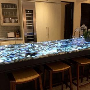 Foto di una cucina minimal di medie dimensioni con ante di vetro, ante in legno chiaro, paraspruzzi verde, paraspruzzi con piastrelle diamantate, elettrodomestici in acciaio inossidabile, isola, top in onice, pavimento in travertino, pavimento beige e top blu