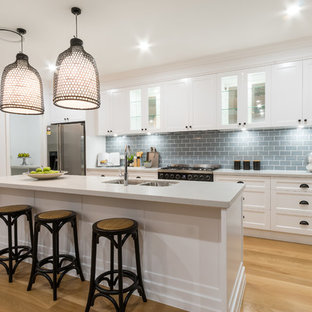 Inspiration for a beach style galley kitchen in Townsville with a double-bowl sink, shaker cabinets, white cabinets, grey splashback, subway tile splashback, stainless steel appliances, light hardwood floors and with island.