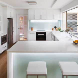 This is an example of a mid-sized transitional u-shaped kitchen in Perth with an integrated sink, recessed-panel cabinets, white cabinets, solid surface benchtops, white splashback, glass sheet splashback, stainless steel appliances, bamboo floors and a peninsula.