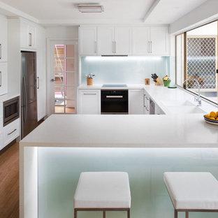 Foto de cocina en U, clásica renovada, de tamaño medio, con fregadero integrado, armarios con paneles empotrados, puertas de armario blancas, encimera de acrílico, salpicadero blanco, salpicadero de vidrio templado, electrodomésticos de acero inoxidable, suelo de bambú y península