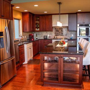 Offene, Mittelgroße Rustikale Küche in L-Form mit Doppelwaschbecken, Schrankfronten im Shaker-Stil, dunklen Holzschränken, Granit-Arbeitsplatte, Küchenrückwand in Beige, Rückwand aus Porzellanfliesen, Küchengeräten aus Edelstahl, dunklem Holzboden und Kücheninsel in Sonstige