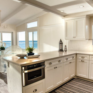 Photo of a mid-sized beach style l-shaped open plan kitchen in San Diego with an undermount sink, white cabinets, quartzite benchtops, white splashback, stainless steel appliances, louvered cabinets, stone slab splashback, medium hardwood floors, a peninsula and grey floor.