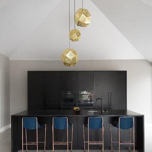 Diseño de cocina actual, de tamaño medio, con armarios con paneles lisos, puertas de armario negras, encimera de granito, electrodomésticos negros, suelo de baldosas de porcelana, una isla y fregadero bajoencimera