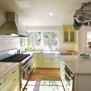 Farmhouse kitchen designs - Example of a country kitchen design in Other with a farmhouse sink, shaker cabinets, yellow cabinets, white backsplash, subway tile backsplash and stainless steel appliances
