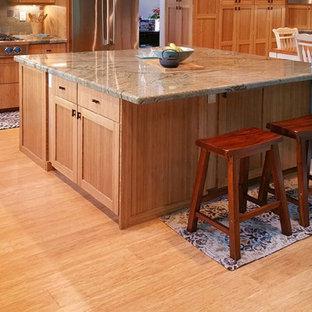 Imagen de cocina en L, actual, cerrada, con puertas de armario de madera clara, encimera de esteatita, salpicadero de azulejos de cemento, electrodomésticos de acero inoxidable, suelo de madera clara, una isla y armarios con paneles lisos