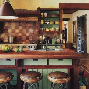 Foto på ett mellanstort rustikt kök, med en undermonterad diskho, släta luckor, gröna skåp, bänkskiva i täljsten, brunt stänkskydd, stänkskydd i metallkakel, rostfria vitvaror, mellanmörkt trägolv och en köksö